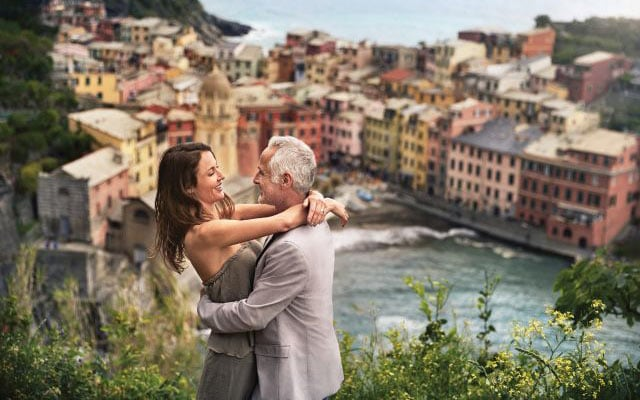 couple hugging with a town in italy in the background