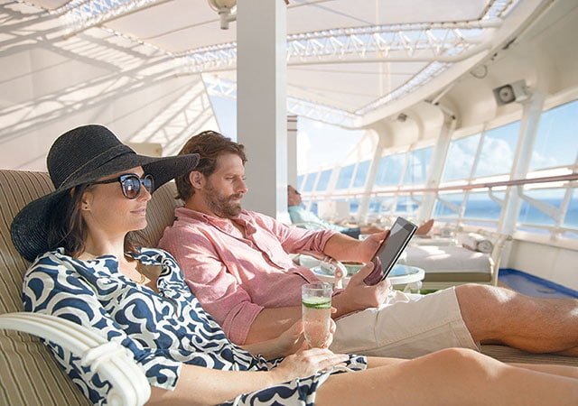 Woman wearing hat and sunglasses, holding glass of cucumber water, next to man wearing shorts and button down shirt holding iPad in lounge chairs in the Sanctuary