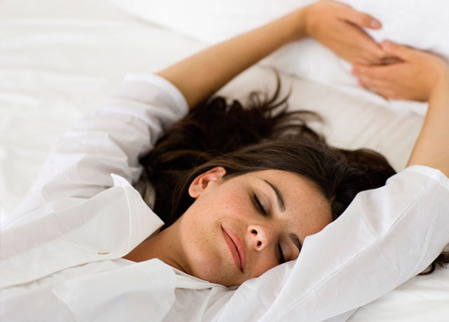 Woman in bed with eyes closed and arms streched over head