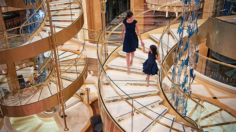 A mother and daughter walking down the spiral stair case hand in hand
