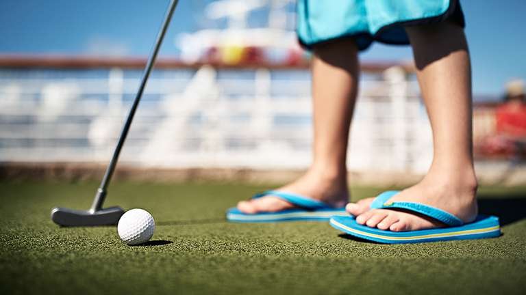 Feet wearing flip-flops, golf club preparing to hit golf ball