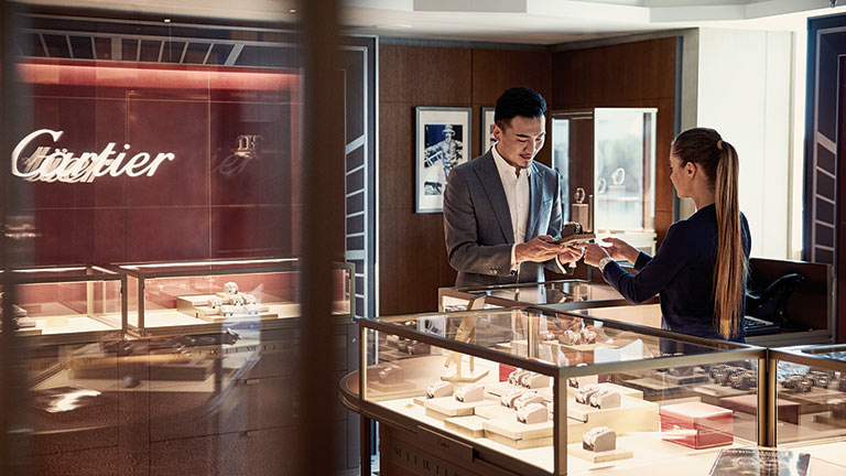 A man with the help of the shop representative looking at a watch inside a retail shop onboard majestic princess