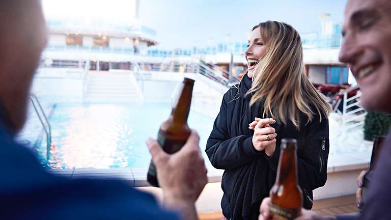Friends sharing a beer poolside.