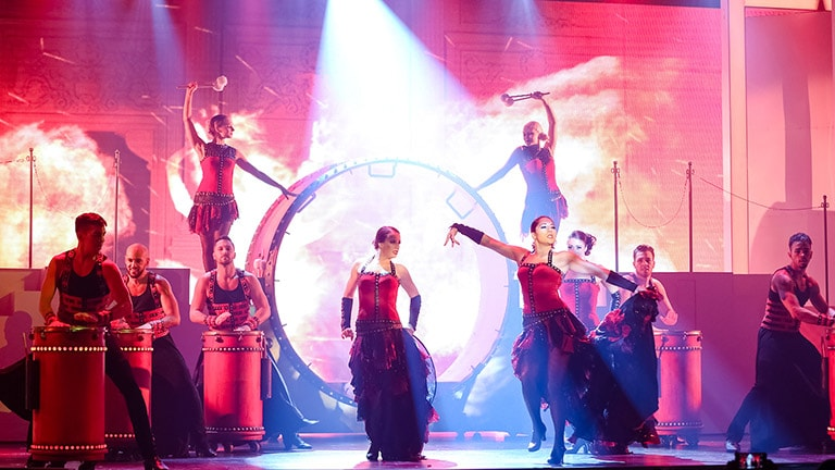 Group of performers on a red lighted stage dancing while others are druming