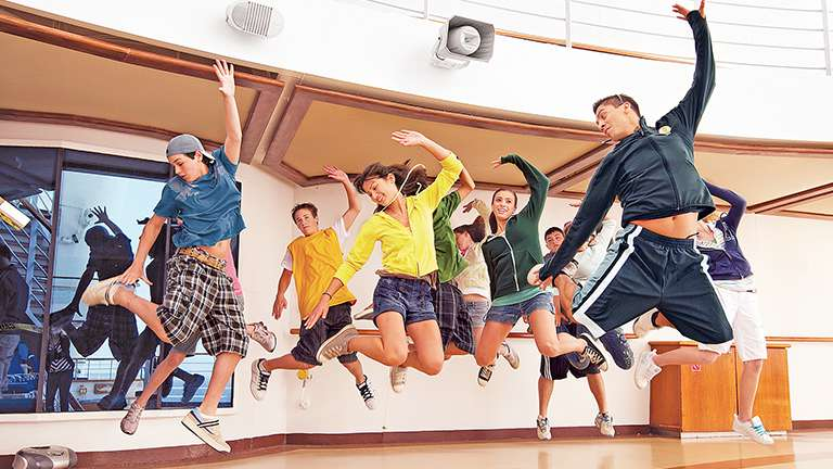 Group of teens jumping in a class on deck